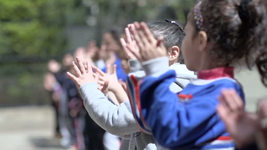 BEIRUT, LEBANON - 2016: Students in elementary school clap while cheering during sports contest at school's playground.