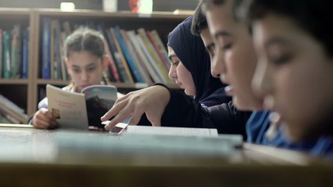 BEIRUT, LEBANON - 2016: Shift focus on students in 6th grade that read books at the school's library. Education in Lebanon is compulsory from age 6 to age 14