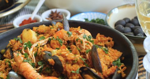 Dolly revealing view of a Spanish seafood paella: mussels, king prawns, langoustine, haddock