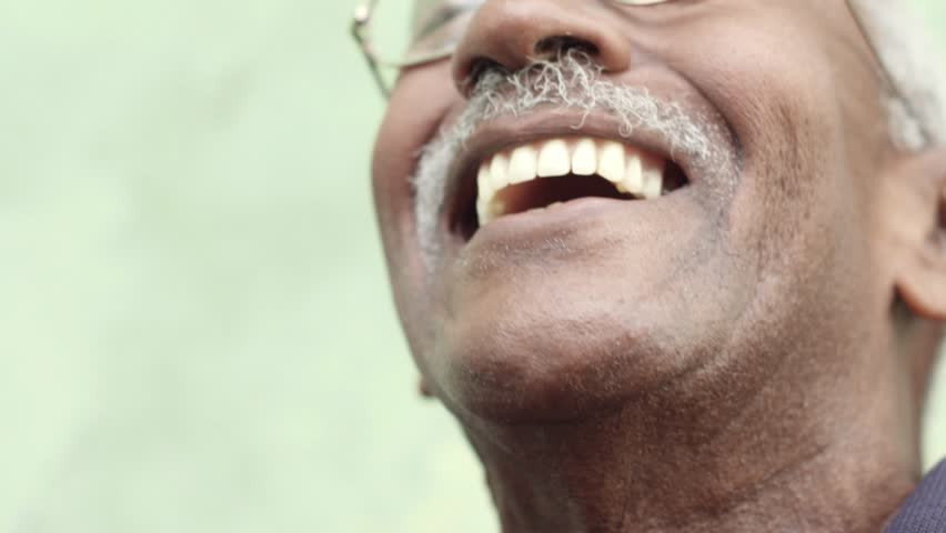 Seniors and feelings, elderly black man with glasses and mustache smiling. Slow motion