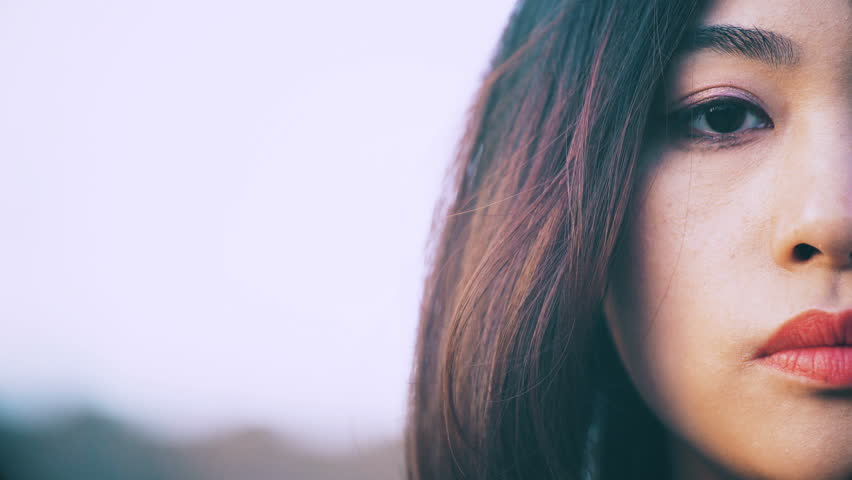 Sad and thoughtful chinese woman with half face outdoor | Shutterstock HD Video #25987163