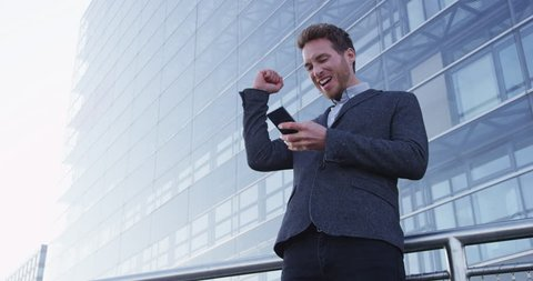 Business success and achievement - happy businessman cheering celebrating on cell phone. Young urban professional successful business man reaching personal goals. Smartphone app or video game concept.