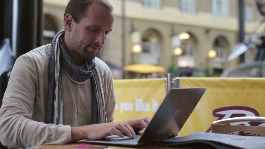 Happy man with laptop in the city