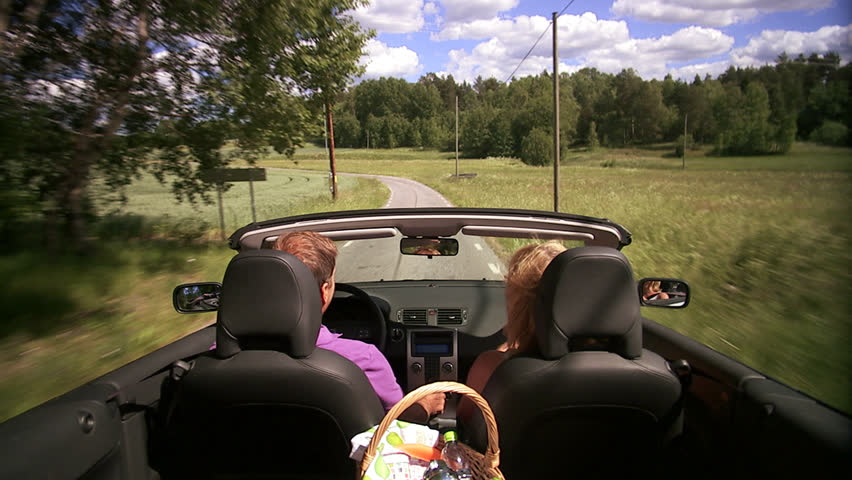 A couple in a convertible car