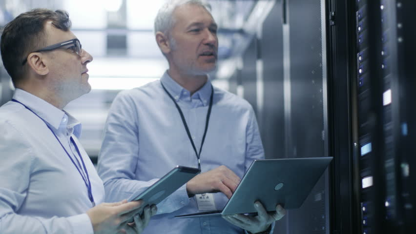 Two IT Technicians Standing in Working Data Center. They Use Laptop and Tablet Computer while Standing Beside Open Server Rack Cabinet.  Shot on RED EPIC-W 8K Helium Cinema Camera.