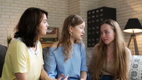 Two young woman bear up and calm down their best unhappy friend who is upset and depressed because of trouble and is needed a moral support, sitting on sofa at home during sunny day