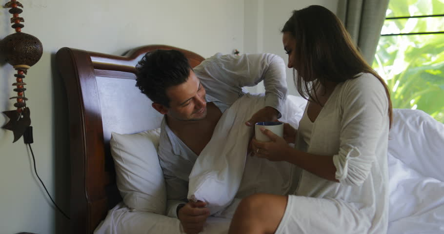 Young Woman Coming To Bedroom With Cup Waking Man, Girl Bring Guy Coffee, Couple In Morning Slow Motion 60 #26110973