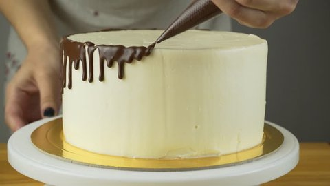 Chocolate icing on the cake. White cake covered with chocolate and cream. Chocolate cake decoration.
