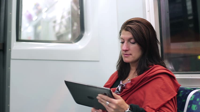 Young woman using tablet computer on subway train