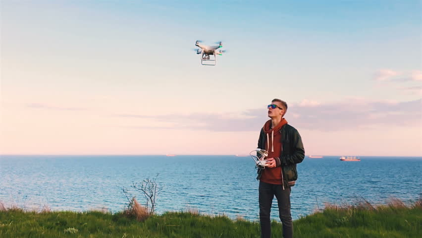 Quadrocopter drone takes off from the pilot's hand and hovers over the guy at sunset. The guy starts a drone on a green glade against the backdrop of the sea and cargo ships. Slow motion (90 fps).