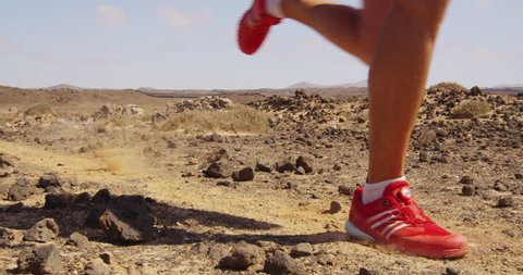 Running man trail running in desert - male athlete runner sprinting fast. Close up of legs and running shoes with dust and rocks flying in SLOW MOTION. RED EPIC.