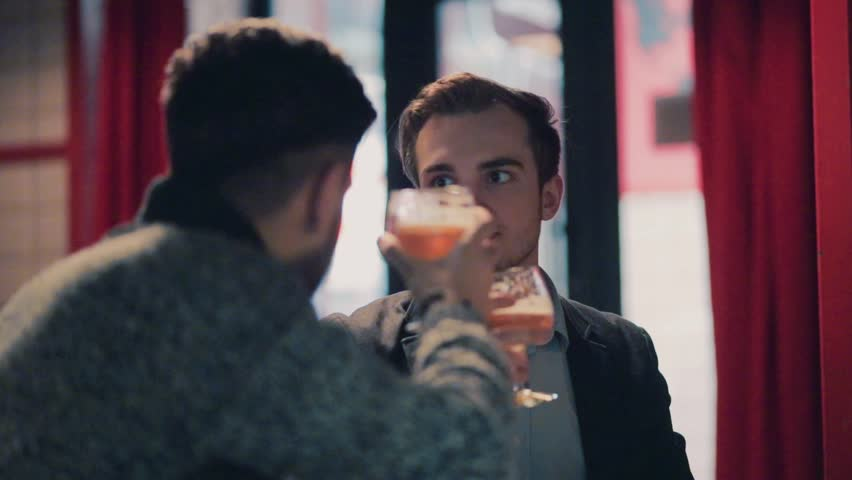 Young handsome male friends having an active discussion while sitting in the bar, they raise their glasses to toast, drink the beer and are surprised with the taste. Man's club, male friendship. | Shutterstock HD Video #26157173