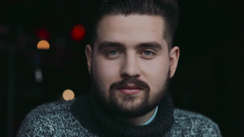 Young attractive blue-eyed bearded man in a warm sweater drinks beer, is surprised with the taste, looks right towards the camera. Bar interior on the background. Man's club, male traditions. | Shutterstock HD Video #26157203