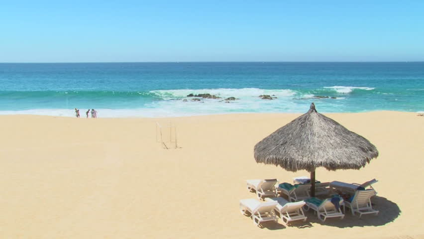 Unrecognizable people enjoy perfect blue sky day at the beach in Cabo San Lucas, Mexico by resort.
