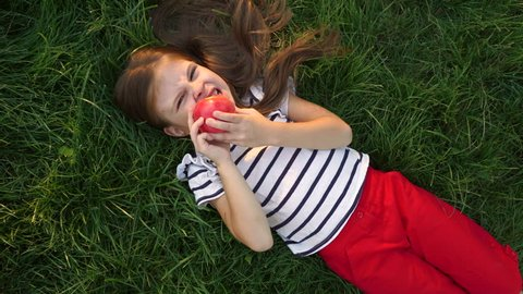 Little girl is eating an apple lying on the green grass in the park. Have a bite in the open air.