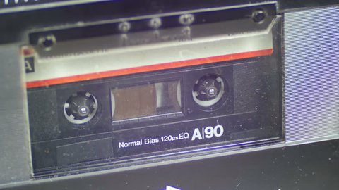 Audio Tape. Vintage tape recorder plays the tape inserted therein. Macro static camera view of vintage audio cassette tape with a blank white label in use sound recording in a cassette player.