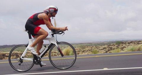 Triathlon biking - male triathlete cycling on triathlon bike. Fit man cyclist on professional triathlon bicycle wearing time trail helmet for ironman race. From Big Island Hawaii. SLOW MOTION RED EPIC