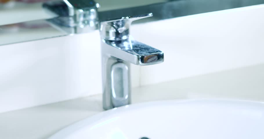 video footage of woman hand open a water tap in the bathroom at home