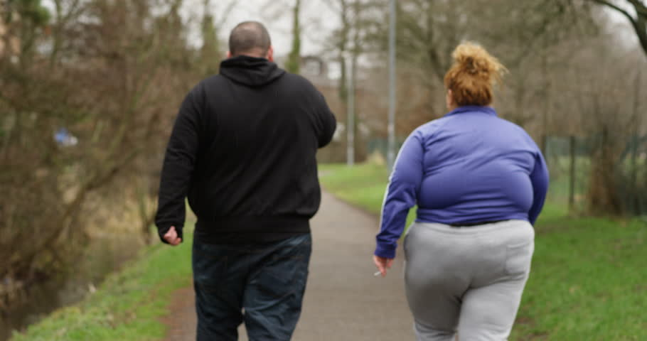 4K Obese couple walking away from camera, smoking cigarettes outdoors in the park. Social issues, unemployment & unhealthy lifestyle concept. Slow motion. | Shutterstock HD Video #26207174