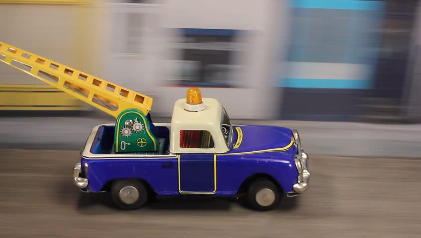 Tin toy breakdown truck towing a car along a urban road with emergency light flashing.