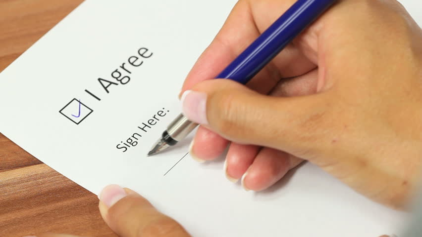 "Female hand checking the ""I agree"" checkbox and applying a signature on the line below"