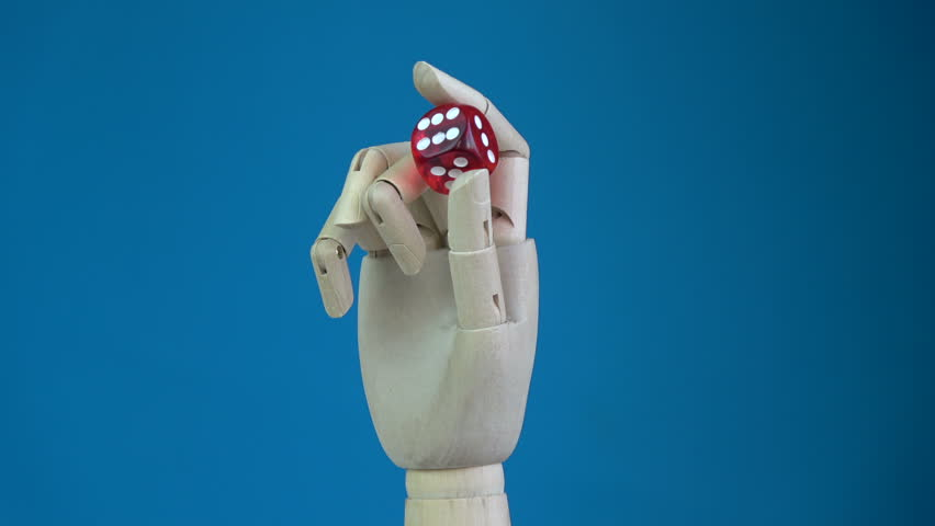 Rotating wooden manikin hand with red lucky game dice