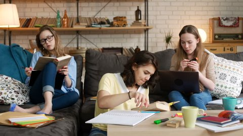 three young female student study together, making notes, working on computer laptop, reading book, to prepare for exam test, being serious and concentrated, while sitting on sofa and on floor in room