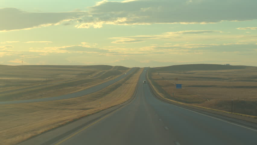 POV Road trip on sunny autumn morning, driving through scenic vast grasslands Great Plains in United States. Traveling along the empty interstate highway through serene countryside on beautiful day