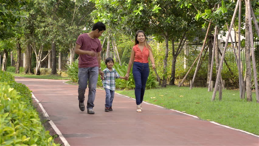 Dolly shot of a happy young Asian family walking together in a park.