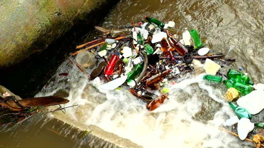 Plastic bottles and another mess turning on water level. Turning of dirty water above weir on small river with muddy water. Stony wall of weir