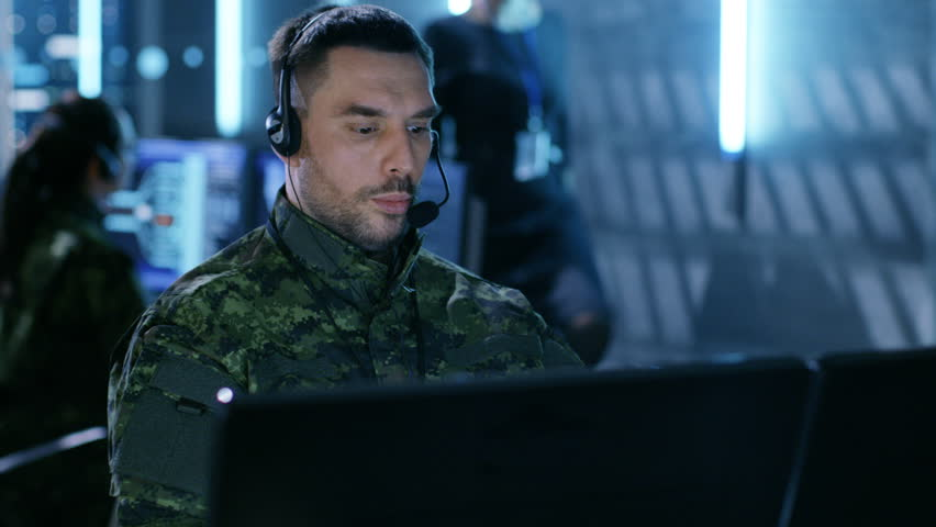 Military Technical Support Professional Gives Instructions Using Headset. He's in a Monitoring Room with Other Officers and Many Working Displays in Background. Shot on RED EPIC-W 8K Helium Cinema.