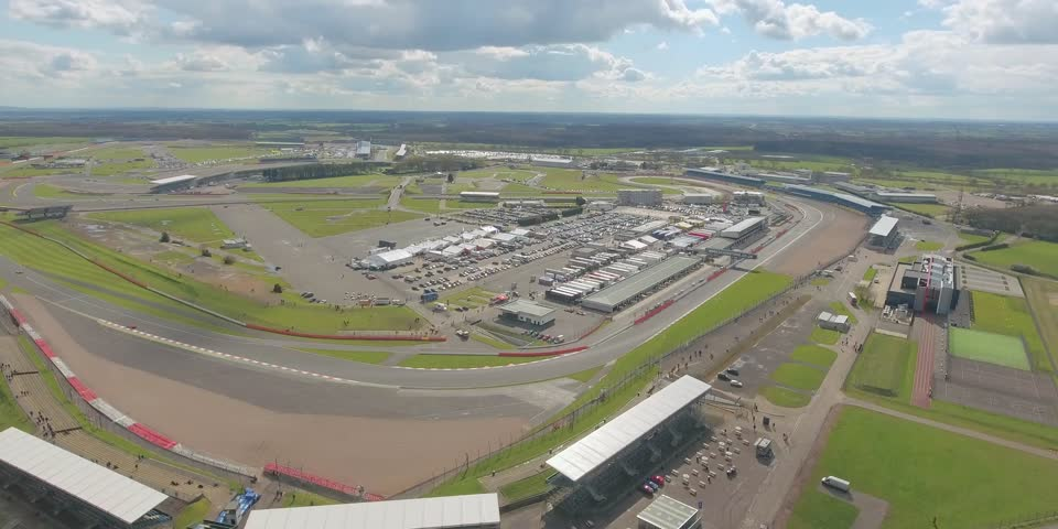 Aerial view of a big race on a sunny summer day in England. Cars going along the race. Full campsite.