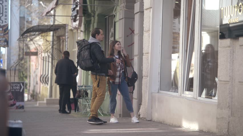 KHERSON, UKRAINE - APRIL 25, 2017: Young travelers walking street looking at showcase of boutiques touristic place of Europe | Shutterstock HD Video #26293634
