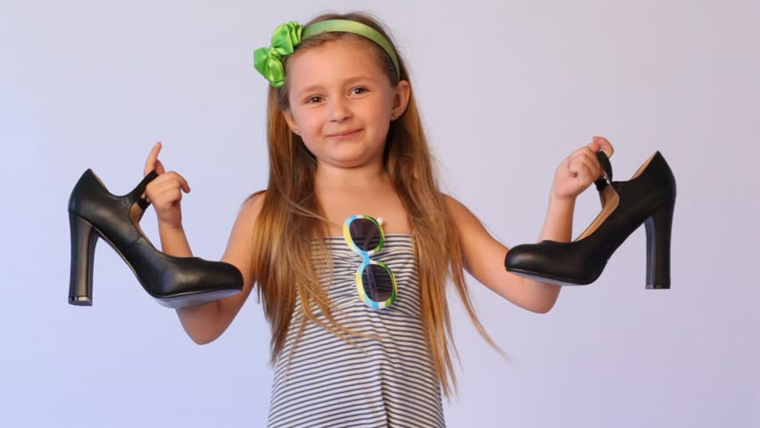 little girl in striped dress in green rim holds in each hand on big black shoe and smile