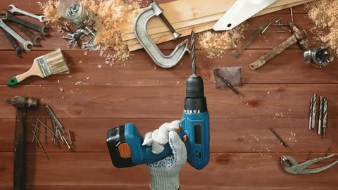 Top view craftsman hand holding a drill and turns it on