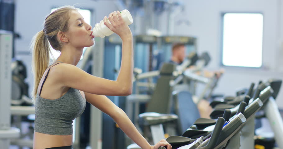 Woman drinking water during ride on stationary bike in gym stock young beautiful girl in a gym shakes her legs on a cycling simulator drinks sciox Choice Image