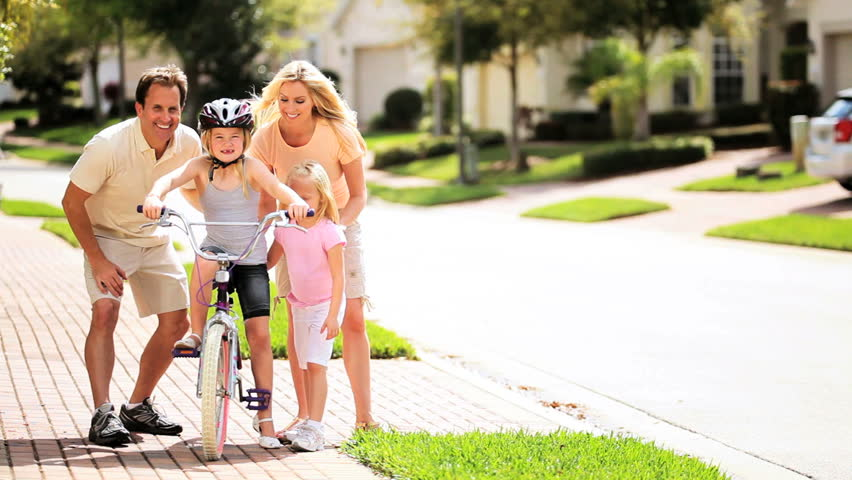 Caucasian parents little blonde girl encouraging older sister practicing bicycle riding