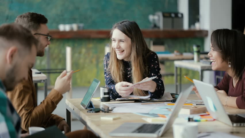 Creative business team meeting in modern office. Mixed race group of young people discussing start-up ideas, laughing. | Shutterstock Video #26337803
