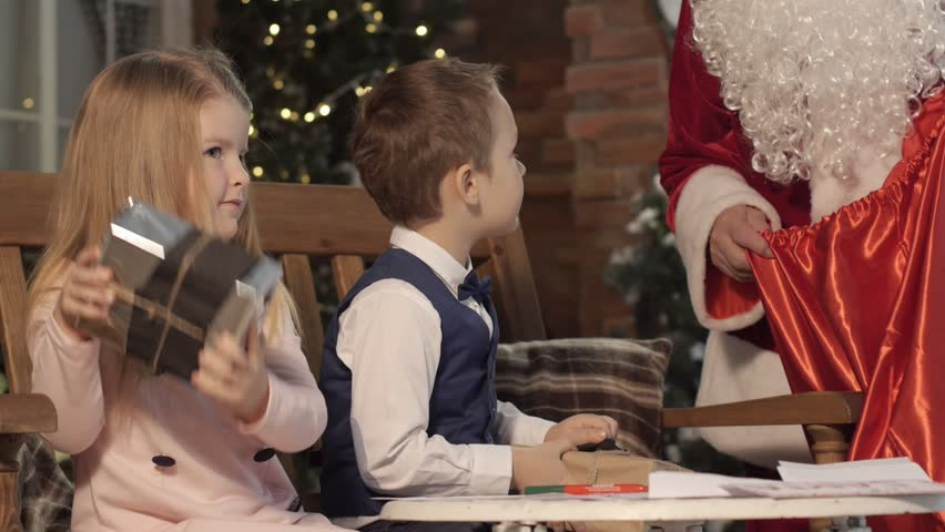 Kids Shaking Christmas Gift Boxes, Santa Claus is Taking Them From a Red Bag. Man Entertains Kids and Parents, Actor Dressed in Red Clothes With Beard Attached and in Glasses. Traditional Celebration | Shutterstock HD Video #26340023