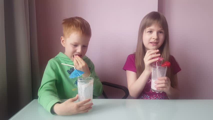 Pair of Young Child (Male and Female) Drink Milk Shake Together Indoor From Glass Tall Cups With Decorations (Strawberry,paper Umbrella). There is a Pink Wall in the Back. They Are Happy | Shutterstock HD Video #26347733