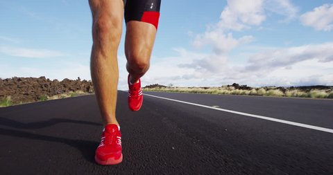 Running shoes on male triathlete runner - close up of feet running on road. Man jogging outside exercising training for triathlon ironman. SLOW MOTION RED EPIC.