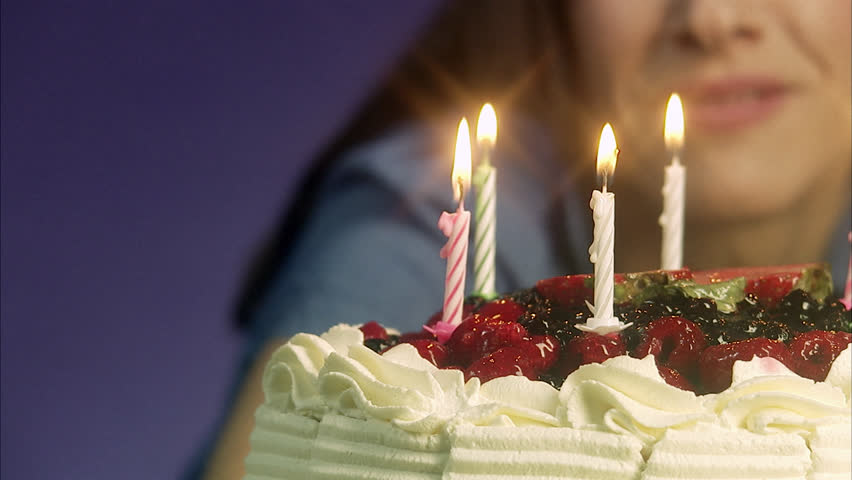 Woman lightening a birthday cake
