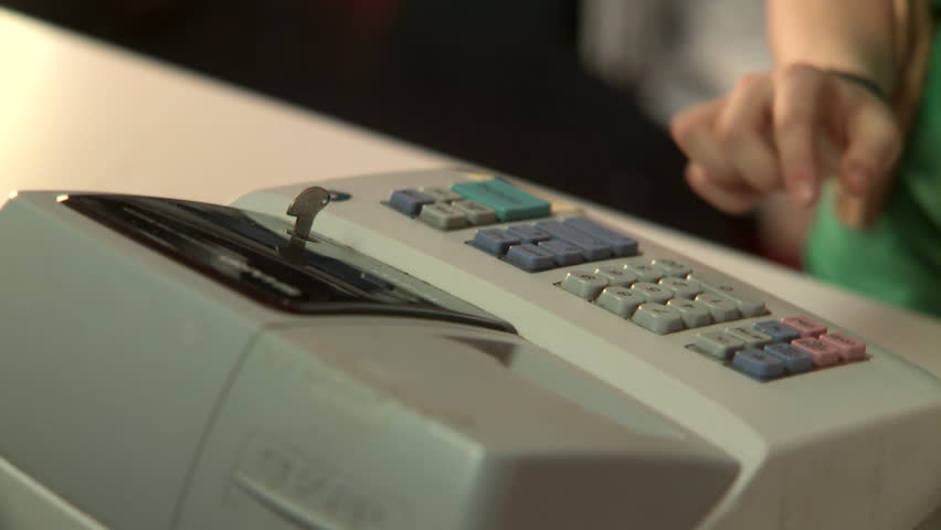 A human hand working a cash register and receiving money