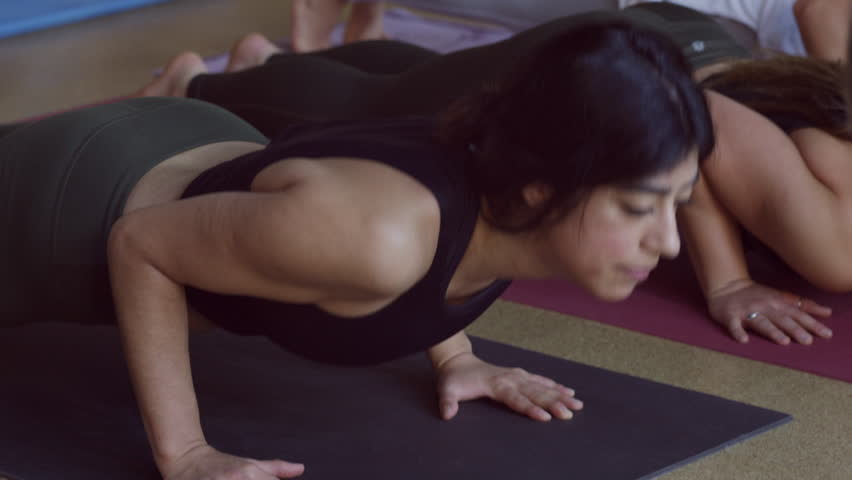 Close up slow motion shot of yoga class changing poses / Provo, Utah, United States