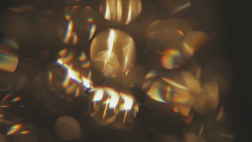 Moving bokeh lights - abstract animation for background - circles of light crossing the frame form left to right - white lights and pastel colors - animation progressively blurs and slows down.
