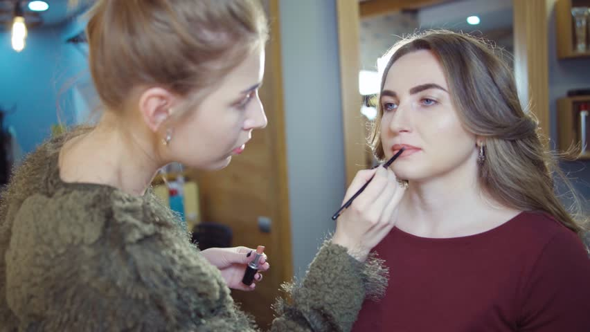 Make up artist doing professional make up of young woman | Shutterstock HD Video #26410493