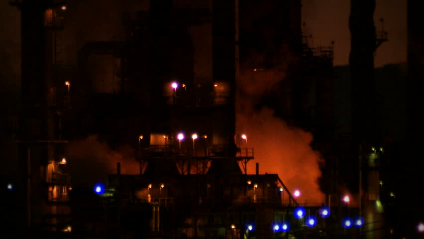 Water canons extinguish a fire burning at an oil refinery in Richmond, California, at night.
