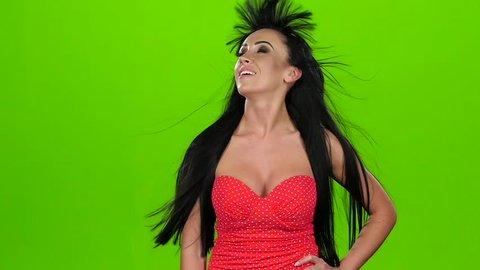 Brunette in corset blows by wind. Green screen, slow motion