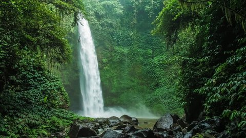 Amazing Nungnung waterfall, Falling water hitting water surface, some huge rocks seeable in front of frame. Lush green leafes is moving from the wind, Bali, Indonesia