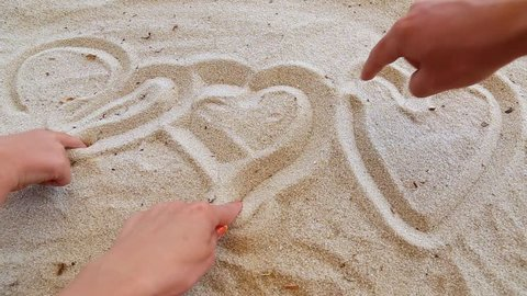 Closeup of tanned human hands of family of three persons. Father, mother and little son drawing heart shapes in sand on river beach. Love and togetherness concept. Real time full hd video footage.